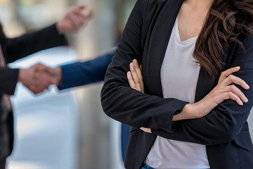 Business woman cross arm with business partner in background.