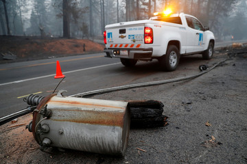 An electricity pole damaged by the Camp Fire lies near a Pacific Gas & Electric truck in Paradise