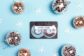 Audio cassette tape with winter holidays decorations on a blue background. Music for winter mood and party.