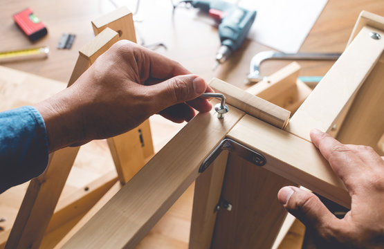 Man assembly wooden furniture,fixing or repairing house with screwdriver tool.modern living concepts