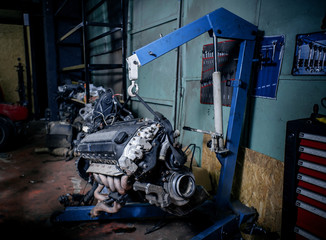 Engine instalation on blue crane hook on car repair service