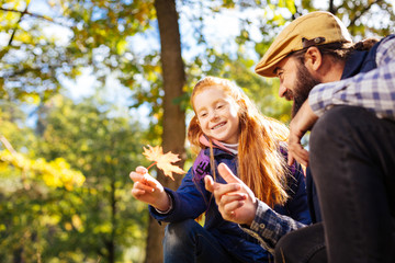 Autumn season. Cute red haired girl holding an orange leaf while sitting together with her dad