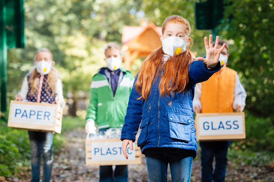 Against pollution. Nice red haired girl wearing a mask while showing her hand to you