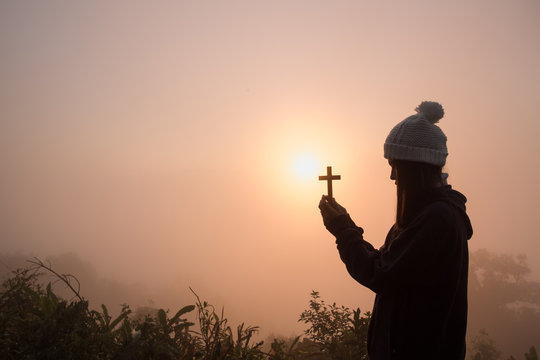 Silhouette of young woman praying with a  cross at sunrise, Christian Religion concept background.