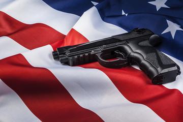 Handgun lying on American flag. Weapon problem concept