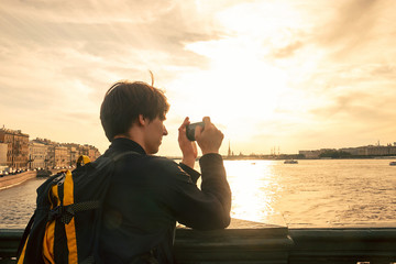 man tourist taking a picture of the seaport bridge above a river in st. petersburg