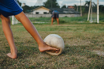 An action picture of a group of kid playing soccer football for exercise in community rural area.