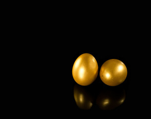 Golden eggs with copy space on black background.