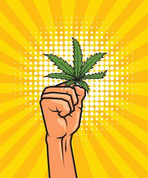 Fist held high hold on cannabis leaf.