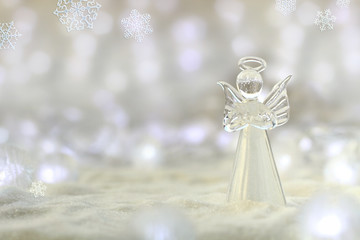 Merry Christmas & Happy New Year greeting card with copy space. Little angel in the white glitter bokeh background.