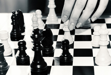 Female hand moves a chess piece on a chessboard indoors. Tinted photo.