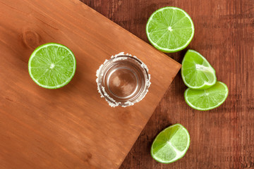 A tequila shot with limes, shot from above on dark rustic textures with a place for text