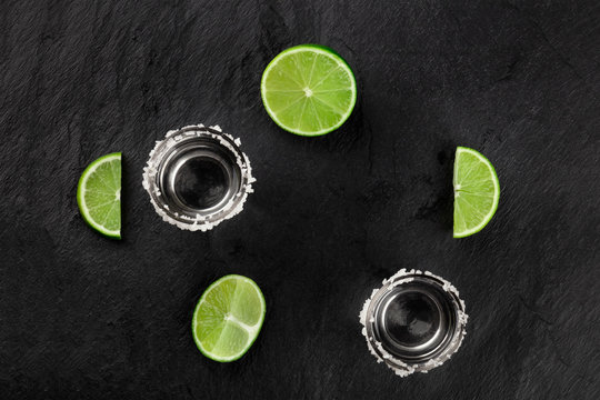 A photo of tequila shots with limes, shot from above on a black background, forming a frame with a place for text