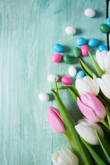 tulips and easter candies on wooden surface
