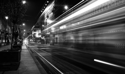 Light trails of a tram driving a street by night (black & white)