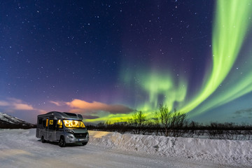 Beautiful green northern lights and camper with light