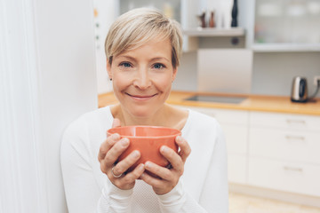 Happy healthy woman with bowl of beverage or soup