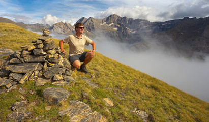Resting tourist on the ridge next to the stone pile with mountains on backround, Pyrenees