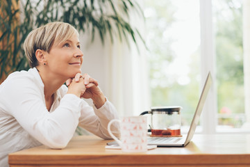 Happy mature woman sitting thinking deeply