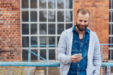 Smiling casual man reading a mobile phone message