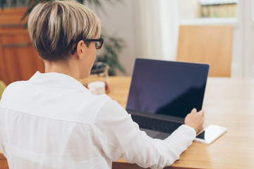 Businesswoman adjusting the screen of her laptop