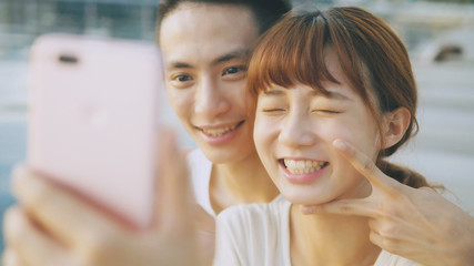 Asian couple using smart phone selfie