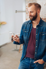 Casual relaxed man in denims using a mobile phone
