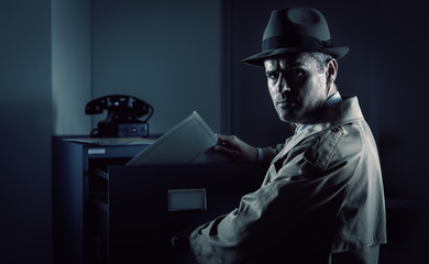 Vintage spy stealing files in the office - fototapety na wymiar