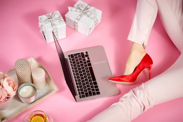 female legs in red high heels, laptop and feminine accessories on a light pink background