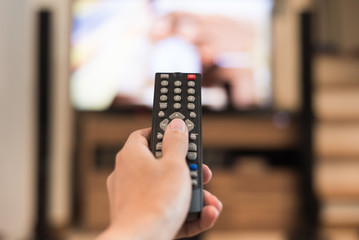 Hand holding remote control with television background in a living room