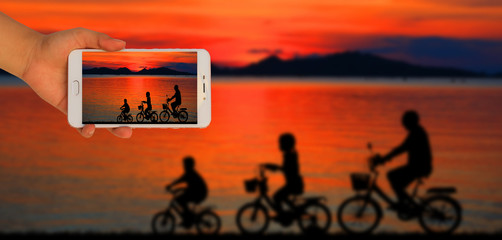 Tourist taking a picture of blur image of silhouette family  riding bicycle on sunset