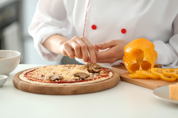 Young female chef cooking tasty pizza in kitchen, closeup