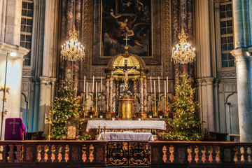 Vienna, Austria - December 24, 2017. Minoritenkirche christmas interior with xmas trees and candles in candelabras. Nationalkirche Maria Schnee or Church of Mary of the Snows decorated altar.