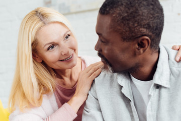 close up of attractive mature woman hugging african american mature man