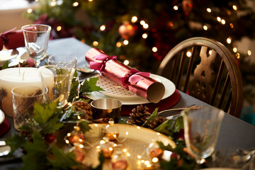 Christmas table setting with a Christmas cracker arranged on a plate with red and green table decorations and a Christmas tree in the background