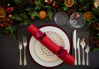 Christmas table setting with a red Christmas cracker arranged on a plate and green and red table decorations, overhead view