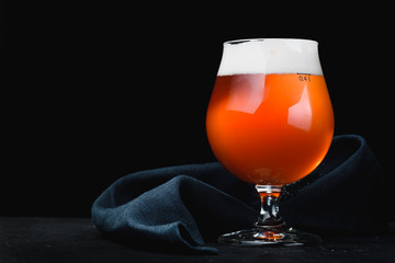 Beer with froth in a glass Snifter isolated on a dark background. close-up. isolated glass of beer