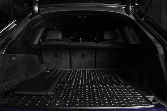 The big black empty trunk of SUV car with rubber mat and with leather folder on the floor  Open luggage carrier of car closeup