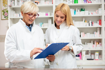 Happy mature and young female pharmacist checking inventory. Mature woman is holding a clipboard and writing. Medicine, pharmaceutics, health care and people concept