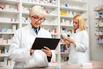 Mature and young female pharmacist working together. Mature woman is using a tablet while young woman reads labels on medication boxes. Medicine, pharmaceutics, health care and people concept
