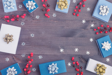 In the center of the wooden background Copy space. Around neatly laid out the twigs of red berries, small gift boxes and snowflakes. Festive layout.