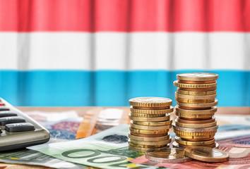 Geldscheine und Münzen vor der Nationalflagge von Luxemburg