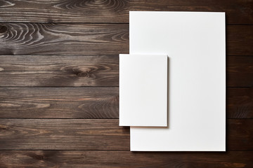 Two white blank canvases on brown wooden background with copy space. Mockup. Front view