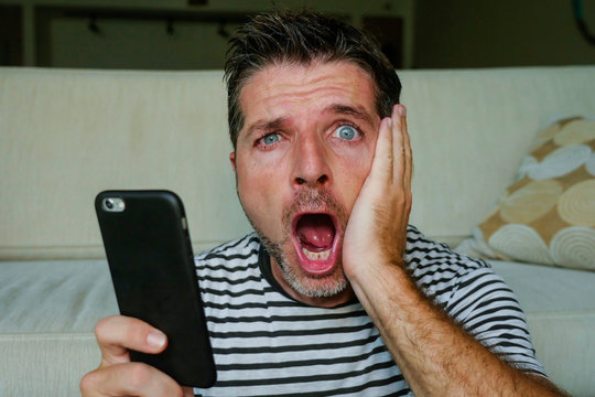 young perplexed and shocked man using mobile phone looking internet social media or checking news in surprised and crazy disbelief face expression feeling petrified