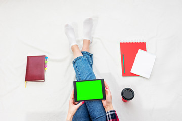 Girl in blue jeans and plaid shirt, holding a tablet PC, women's feet, lying on white crumpled blanket. Women's hands, red manicure, tablet PC, close up. Background with copy space. Top view
