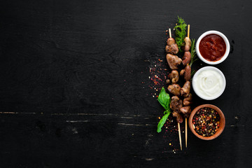 Skewers of chicken heart. On a wooden background. Top view. Free space for your text.