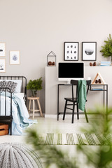 Branches of spruce in glass vase on wooden nightstand between single metal bed with light blue bedding and desk with all in one computer