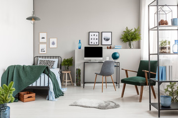 Retro dark green armchair in stylish bedroom interior with single metal bed and desk with computer