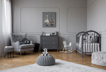 Toy on grey pouf in the middle of trendy baby bedroom with grey wooden cradle, chest of drawers and comfortable armchair, real photo with poster on the wall