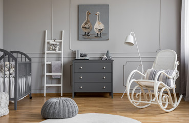 Grey pouf on white carpet inelegant baby bedroom interior with white and grey furniture, real photo
